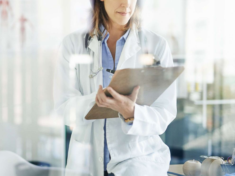 PHOTO: A doctor writes on a clipboard in a consulting room in this undated stock photo.