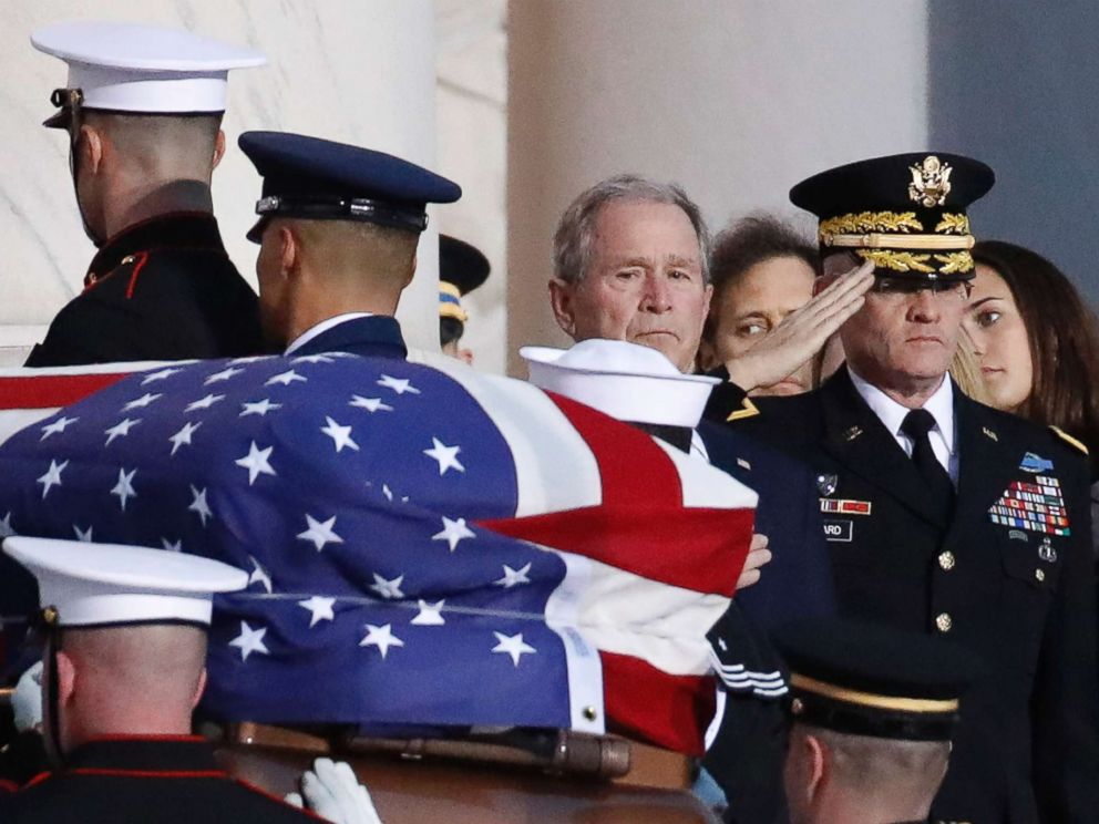 PHOTO: Former President George W. Bush watches as the flag-draped casket of his father, former President George H.W. Bush is carried by a joint services military honor guard to lie in state in the rotunda of the U.S. Capitol, Dec. 3, 2018, in Washington.